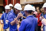 A group of young men in hard hats and safety goggles give each other high-fives.