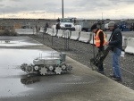Workers with Hanford contractor CH2M HILL Plateau Remediation Company test a robotic crawler on the roof of a former fuel storage bunker. The crawler was used to safely evaluate the load capacity of the roof as part of preparations for future demolition a