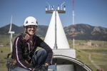 A female researcher with safety equipment crouches on top of a turbine nacelle with a mountain backdrop.