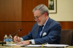 Secretary Brouillette smiles while signing a document