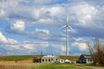 wind turbine on farmland against a cloudy but blue sky.