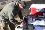 Nye County's John Klenke collects water samples from an Amargosa Valley location.