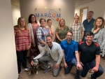 In this photo from February, MarCom employees are shown with the company's mascot, the dog Moxie. MarCom President Marcella Medor is second from left.