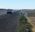 Hanford Site road maintenance worker Chris Bates covers posts with white canvas bags along a section of roadway as part of a pilot project to discourage deer and elk from crossing in front of vehicles.