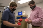 Savannah River Nuclear Solutions (SRNS) Senior Health Physicist Michael Ratliff, left, examines parts created by SRNS Principal Scientist Andy Warren using a 3D printer.