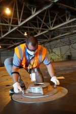 Defense Waste Processing Facility operator Stephen Potter assembles a double-stack plug grapple adapter before a feasibility demonstration.
