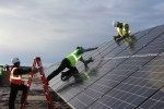 Three workers installing on some solar panels.