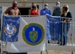 Officials with the Moab Uranium Mill Tailings Remediation Action Project hold up commemorative flags recognizing the milestone of disposing 11 million tons of mill tailings.