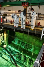 Savannah River Nuclear Solutions operators Thomas Dill, Jack Phillips, and Carl Cato use a long-handled tool to position an underwater vacuum on top of a High Flux Isotope Reactor core in L Basin at the Savannah River Site.