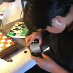 student studies a rock using a smartphone microscope.