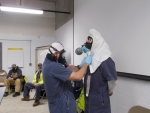 CH2M HILL BWXT West Valley Facility Disposition Supervisor Tim Wittmeyer, left, and co-worker Mike Sexton demonstrate donning and doffing personal protective equipment during a mock-up session at the West Valley Demonstration Project.