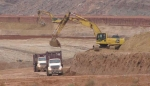 Empty containers on haul trucks are being loaded with mill tailings.
