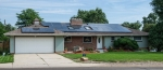 Photo of a home with a residential photovoltaic system installed on the roof.