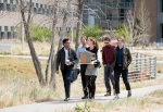 Students walk with their building design in front of the NREL campus.