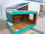 A solar powered dog house on display.