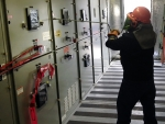 An Idaho Site electrician racks out a breaker so a cubicle can be cleaned as part of preventive maintenance.