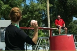 Paducah Cooperative Ministry Executive Director Heidi Suhrheinrich throws a baseball as DOE's Mark Allen sits above the dunking tank.