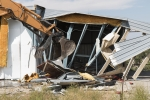 Workers demolish a former radiologically contaminated warehouse at a historic Los Alamos site.