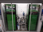 A pilot-scale polymerization reactor sits in the middle, with the ACOMP system on the left side and the control interface on the right side.
