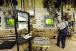 An operator uses robotic manipulators to process RH TRU.