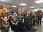 a photo of more than a dozen men and women with camouflage shirts.