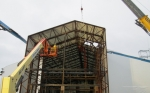 Workers construct an enclosure for Building H2 at the Separations Process Research Unit