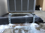 An image of a air source heat pump in the snow