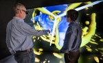 NREL Senior Engineering Project Manager, Pat Moriarty, left and NREL Senior Engineer , Paul Fleming, review velocity (blue) and turbulence (yellow) in a simulation of the Lillgrund Wind Farm in Denmark, in the Visualization Lab in the ESIF at the National Renewable Energy Lab. The researchers have written Open Source software that simulates wind farm conditions.