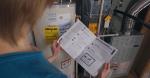 A woman looks at a checklist with a water heater in the background.