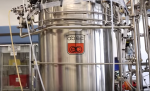 "Fermentation tank from Lawerence Berkeley National Laboratory's Advanced Biofuels Process Demonstration Unit, used by Lygos for pre-pilot testing of malonic acid production. (Photo from ""Enabling the Billion-Ton Bioeconomy"" video; Lygos Founder and CEO, Eric Steen, appears in a segment of the video.)"