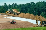 Workers add the geosynthetic layer to the protective mound capping the dirt and coal ash landfill.
