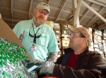 JD Hope (left) and Kevin Carr, with SRNS Regulatory Integration and Environmental Services, prepare a container of fluorescent tubes for recycling at the SRS Recycling Center.