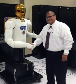 Rimando shakes hand with a Robonaut 2 at Johnson Space Center. It was the first human-like robot NASA launched to space.