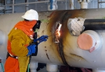 A worker employs a thermal lance to cut apart a massive tank so it can be removed from a building slated for demolition at the Idaho Site's Materials and Fuels Complex.