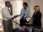 EM employees Carol Ward, right, and Marlenia Murray, center, serve hot dogs and half-smokes as part of the Combined Federal Campaign.