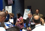 From right, EM's Andre Fordham, Frank Moussa, and Vanessa Jenkins, and other DOE employees, talk with military veterans at DOE's recruitment booth at the hiring event.