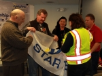 From left, ITG President and Project Manager Dave Richardson assists DOE Idaho Operations Office Deputy Manager of Environmental Management Jack Zimmerman and DOE Idaho Operations VPP Program Lead Carol Henning (in yellow vest) with unfurling the AMWTP's Voluntary Protection Program Star flag. ITG Employee Safety and Improvement Team Co-Chairs Ashlee Murdock and Alan Shaffer are in the background.