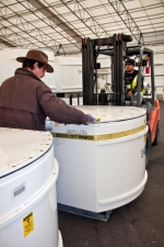Workers move standard waste boxes to the High-Energy Real Time Radiography facility.