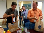 Front, left to right: Tyler Hicks and Rob Swett from DOE's Portsmouth/Paducah Project Office in Lexington pack non-perishable items for donation to local food pantries.