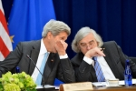 Secretary of State John Kerry and Energy Department Secretary Ernest Moniz talking at a table.