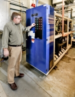 Man standing next to a refrigeration system at the laboratory.