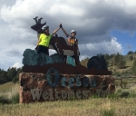 "Rachel Woods-Robinson and Elizabeth Case, the ladies of Cycle for Science, high-five on top of the ""Welcome to Oregon"" sign. 