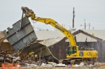 A heavy equipment operator uses a shear to move a large section of wall from the C-746-B warehouse during demolition.