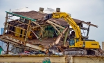 """Once the building was down, heavy equipment operators began """"top-down"""" shearing to safely remove the remaining structure. Demolition debris was then downsized and loaded into rail cars for shipment off site."""