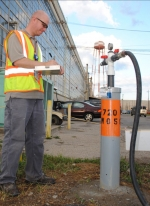 Neil Smith puts a trained eye on the pressure and flow of a food grade compound being injected into an underground plume of hazardous waste near the X-720 Maintenance Facility at the DOE Piketon Site. The sodium lactate compound promotes bacterial growth in the groundwater that turns hazardous waste into harmless end-products.