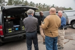 Savannah River National Laboratory (SRNL) Manager of Homeland Security Charles Lewis (from left); a Florida Highway Patrol participant; SRNL Technical Advisor Carl Jacobs; and a Domestic Nuclear Detection Office sponsor discuss the setup of the detection equipment in an SUV.