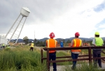 Workers observe the demolition of the West Water Tower at Los Alamos National Laboratory.