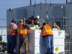 Workers with Richland Operations Office contractor CH2M HILL Plateau Remediation Company load a piece of glovebox into a large standard waste box for transportation and disposal. The glovebox was removed from Hanford's Plutonium Finishing Plant, a former plutonium processing plant workers are preparing for demolition.