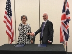 Acting EM Assistant Secretary Sue Cange and Rob Buckingham, director of the Center for Remote Applications in Challenging Environments, shake hands after signing the Statement of Intent.