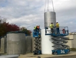 Workers load an overpack container into a vertical storage cask.